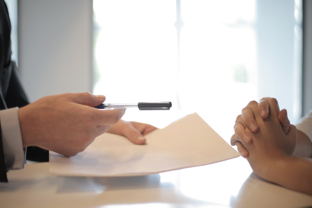 Dois pares de mãos. Uma segura uma caneta e um documento.